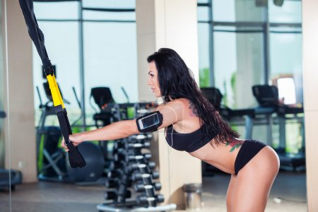 attractive woman does crossfit push ups with trx fitness straps in the gyms studio