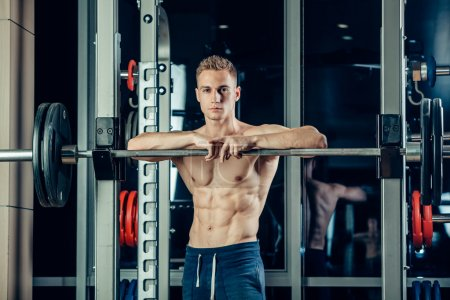 Closeup portrait of a muscular man workout with barbell at gym. Brutal bodybuilder athletic six pack, perfect abs, shoulders, biceps, triceps and chest
