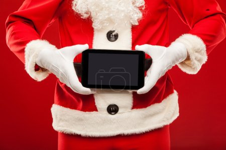 Photo for Santa Claus holding tablet, red background, hands - Royalty Free Image