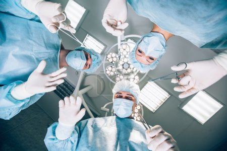 Surgeons standing above of the patient before surgery