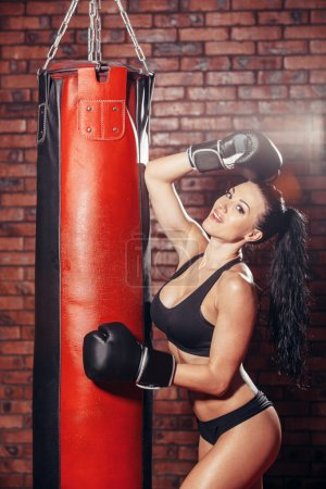 Young sexy girl with boxing gloves, punching bag, on the background wall of red brick.