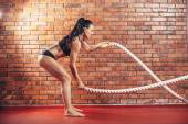 Attractive young and athletic girl using training ropes in a gym, on the background wall of red brick.