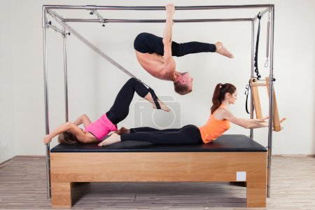 Pilates aerobic instructor a group of three people in cadillac fitness exercise