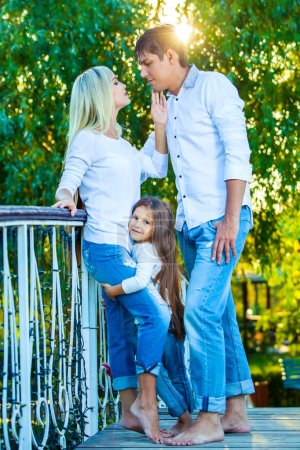 Mom, Dad and kid laughing hugging, enjoying nature outside. in blue jeans white shirts