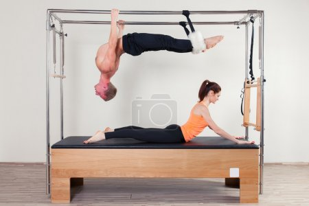 Pilates aerobic instructor woman and man in cadillac fitness exercise