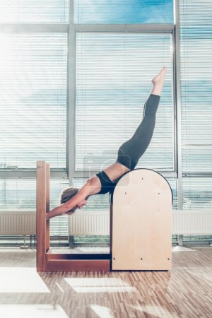 Pilates, fitness, sport, training and people concept - smiling woman doing  exercises on ladder barrel