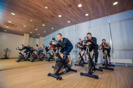 Group of gym people on machines, cycling In Class