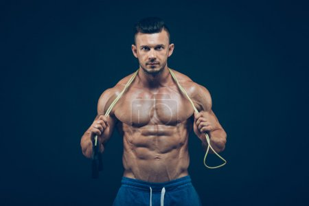 Muscular man skipping rope. Portrait of muscular young men exercising with jumping rope on black background