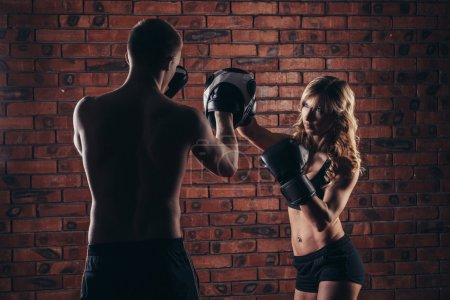 Photo for Cute brunette woman training with boxing gloves at the gym against brick wall - Royalty Free Image