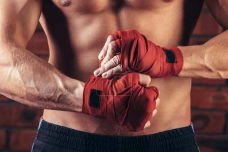 Photo for Muscular Fighter With Red Bandages against the background of a brick wall - Royalty Free Image