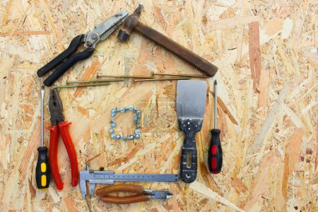 Construction tools in the form of house on wooden background. construction tools: pliers, hammer, pruner, screws, putty knife and ruler.