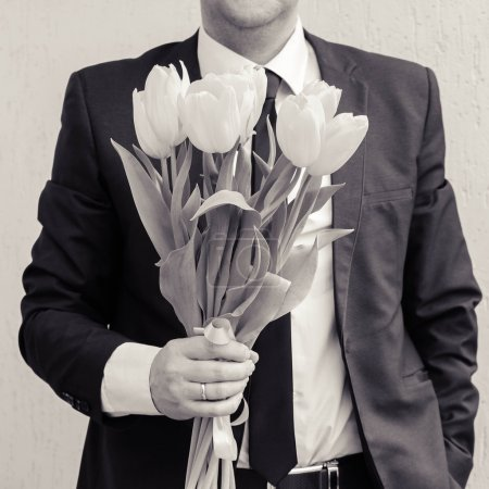A man wearing a business suit, holding a bouquet of tulips. The man gives a bouquet of flowers. Black and white shot.
