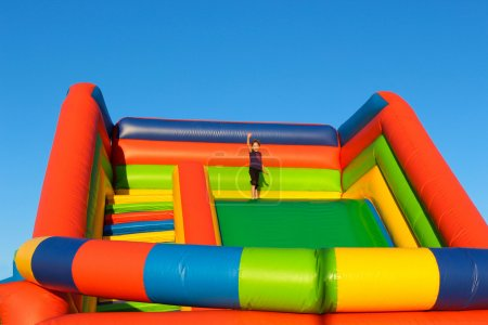 A little girl stands on an inflatable trampoline. The child welcomes hand on high the children slide.