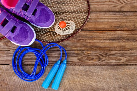 Photo for Sports equipment: the birdie is on the racket, skipping rope and sneakers on wooden background - Royalty Free Image
