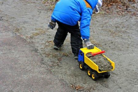 Chico jugando con juguete camión .
