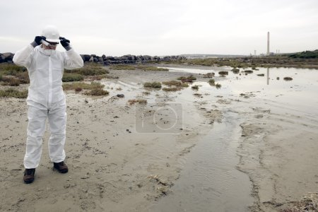 Worker in a protective suit examining pollution