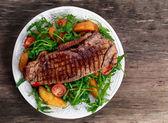 Vzácné hovězí steak s pečenými bramborami, rajčaty a rukola listy. na starý dřevěný stůl
