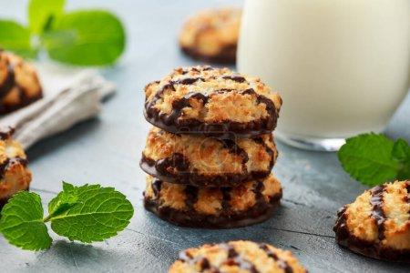 Kokosmakronen-Kekse mit einem Schuss Schokolade, serviert mit einem Glas Milch. Glutenfrei