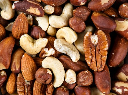 Natural background texture made from mixed kinds of nuts - pecans, hazelnuts, walnuts, cashews, almonds, pine nuts, pistachios