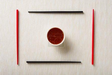 Photo pour Baguettes et bol avec sauce sur le tapis de table vue du dessus - image libre de droit