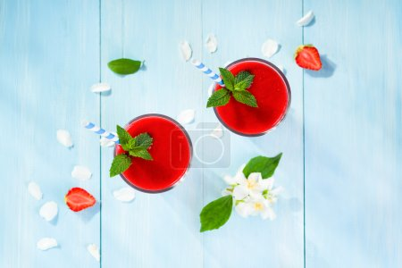 Strawberry smoothie and flower petals on blue back...