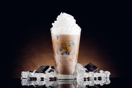 Photo for Iced coffee in glass and crushed ice on brown background - Royalty Free Image