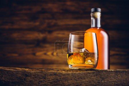 Photo pour Verre à whisky et bouteille sur la vieille table en bois - image libre de droit