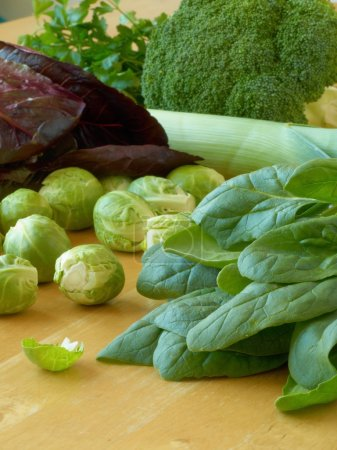 Photo for Leafy vegetables - spinach, Brussels sprouts, leeks, parsley, broccoli, lettuce - lying on a wooden table - Royalty Free Image