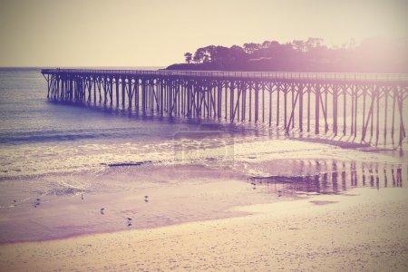 Vintage wood bridge at beach sunset, California, USA.