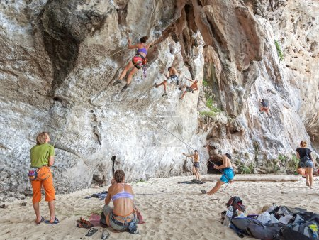 Rock climbers climbing the wall on Railay beach.