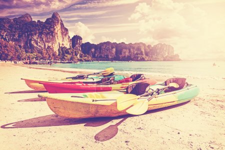 Retro toned kayaks on a tropical beach.