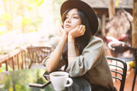Woman drinking coffee in the garden outdoor in sunlight light en