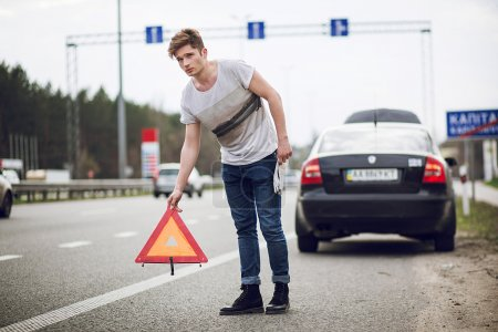 Photo for A car with a breakdown alongside the road, man sets the warning triangle - Royalty Free Image