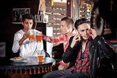 Společnost v baru. mluvení na telefonu