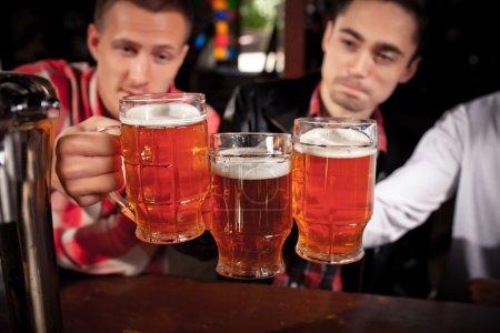 Photo pour Amis heureux cliquetis avec des tasses de bière dans le pub, souriant . - image libre de droit