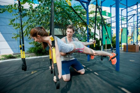 people does suspension training with fitness straps outdoors