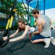 Постер, плакат: people does suspension training with fitness straps outdoors