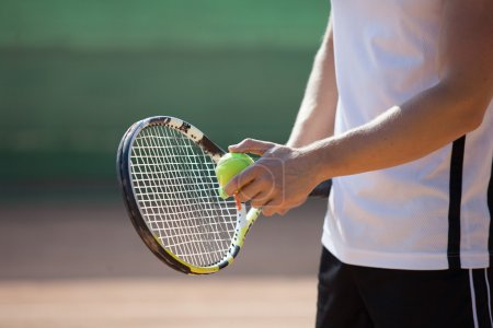 Players hand with tennis ball preparing to serve