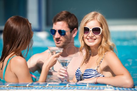 guy flirting with two women at  swimming pool, drinking