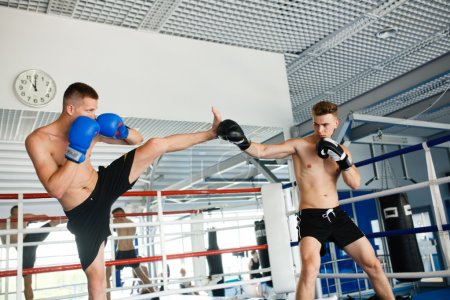 Photo for Sport and people, two men exercising and fighting in boxing gym - Royalty Free Image