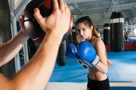 Photo pour Femme séduisante poinçonnant un sac avec des gants de boxe sur - image libre de droit