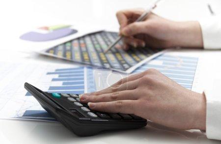 Photo pour Photo de la jeune femme d'affaires calculant les documents financiers - image libre de droit