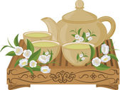 Kettle small cups of green tea on a wooden table and flowers of tea Set of isolated objects