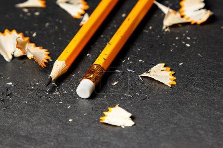Photo pour Deux crayons avec des copeaux sur fond noir. Image horizontale . - image libre de droit