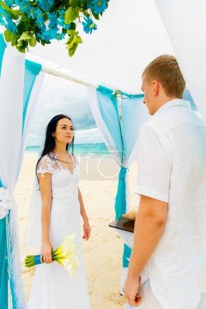Photo pour Cérémonie de mariage sur une plage tropicale bleue. Joyeux marié et mariée sous l'arche décorée de fleurs sur la plage de sable fin. Concept de mariage et lune de miel . - image libre de droit