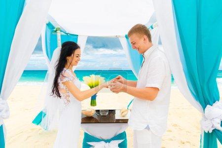 Photo pour Balancent donnant une bague de fiançailles à sa mariée sous l'arche décorée de fleurs sur la plage de sable fin. Cérémonie de mariage sur une plage tropicale bleue. Concept de mariage et lune de miel . - image libre de droit