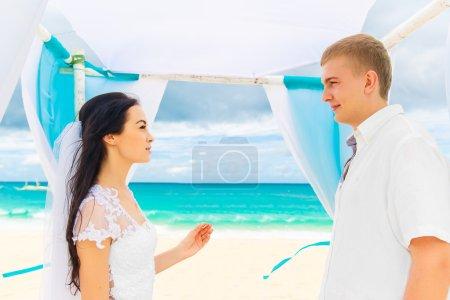 Photo pour Mariée donnant une bague de fiançailles à son marié sous l'arche décorée de fleurs sur la plage de sable fin. Cérémonie de mariage sur une plage tropicale bleue. Concept de mariage et lune de miel . - image libre de droit