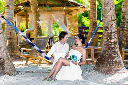 Happy bride and groom having fun in a hammock on a tropical beac
