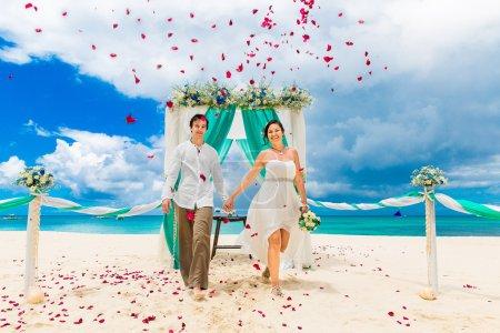 Photo pour Cérémonie de mariage sur une plage tropicale bleue. Joyeux marié et mariée sous l'arche décorée de fleurs sur la plage de sable fin. Les pétales de rose tombent d'en haut. Concept de mariage et lune de miel . - image libre de droit