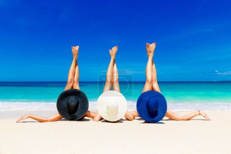 Photo for Three young women in straw hats lying on a tropical beach, stretching up slender legs. Blue sea in the background. Summer vacation concept. - Royalty Free Image